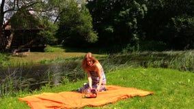 Dziewczyna siedzi na pomarańczowym dywaniku, owocowa gronowej bonkrety wazowa pobliska bieżąca rzeka zbiory