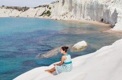 Dziewczyna siedzi na skłonie dzwoniącym biała faleza & x22; Scala dei Turchi& x22; w Sicily Obrazy Stock