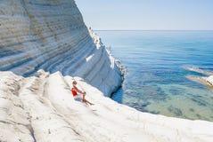 Dziewczyna siedzi na skłonie dzwoniącym biała faleza & x22; Scala dei Turchi& x22; w Sicily Fotografia Stock