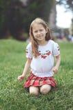 Dziewczyna siedzi na trawie w parku i spojrzeniach przy kamerą fotografia stock