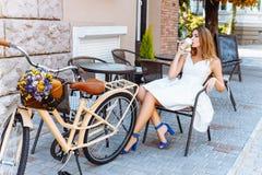 Dziewczyna siedzi na ulicie z kawą i bicyklem Zdjęcie Royalty Free