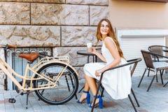 Dziewczyna siedzi na ulicie z kawą i bicyklem Obrazy Stock