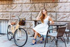 Dziewczyna siedzi na ulicie z kawą i bicyklem Zdjęcie Stock
