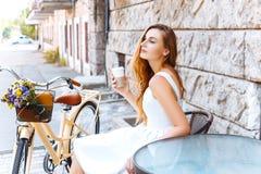 Dziewczyna siedzi na ulicie z kawą i bicyklem Zdjęcia Royalty Free