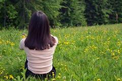 Dziewczyna siedzi na zielonym gazonie blisko lasu widoku Z powrotem Obraz Royalty Free