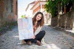 Dziewczyna siedzi na ziemi i pokazuje mapę Fotografia Royalty Free