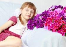 Dziewczyna siedzi obok bukieta kwiaty Fotografia Stock