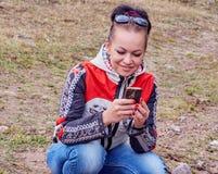 dziewczyna siedzi patrzejący telefon obraz stock