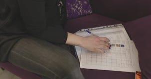 Dziewczyna siedzi pracuje z dokumentami na kanapie w górę zbiory wideo