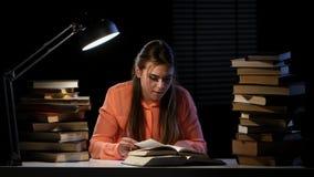 Dziewczyna siedzi przy stołem i no może znajdować pragnącą informację Czarny tło zbiory wideo