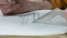 Dziewczyna siedzi przy stołem i rysuje jej zadanie w notatniku zbiory wideo
