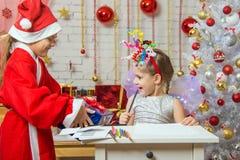 Dziewczyna siedzi przy stołem z fajerwerkami na głowie, Święty Mikołaj dać ona prezentowi Fotografia Royalty Free