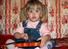 dziewczyna siedzi sofa skrzypce. Zdjęcie Stock