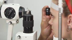 Dziewczyna siedzi spokojnie podczas biomicroscopy ankiety oczy zbiory