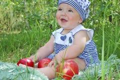 Dziewczyna siedzi w birchwood na trawie i je jabłka Zdjęcia Royalty Free