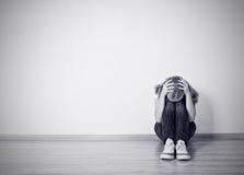 Dziewczyna siedzi w depresji na podłoga blisko ściany obraz stock