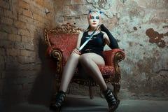 Dziewczyna siedzi w krześle, trzyma kordzika jego ręka Zdjęcia Royalty Free