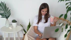 Dziewczyna siedzi w krześle z laptopem i trzyma filiżankę w jej rękach, domowy wnętrze, zwolnione tempo zbiory