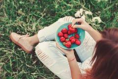 Dziewczyna siedzi w lato trawie i trzyma talerza w cajgach truskawki, kolana i ręki widoczni, Zdrowy śniadanie, Zdjęcie Stock