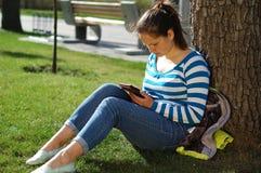 Dziewczyna siedzi w parku i czyta ebook fotografia stock