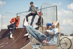 Dziewczyna siedzi w wózek na zakupy i pije od puszki w hełmofonach podczas gdy przyjaciele ma zabawę na rampie Zdjęcie Stock