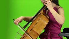 Dziewczyna siedzi wiolonczelę i bawić się zielony ekran Boczny widok zdjęcie wideo