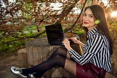 Dziewczyna siedzi z laptopem w naturze Zdjęcie Stock