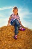 Dziewczyna siedzi z nogami krzyżować na słomianej piłce Fotografia Royalty Free