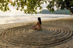 Dziewczyna siedzi z powrotem na piaskowatej plaży w centrum improwizowany okrąg i medytuje obraz royalty free