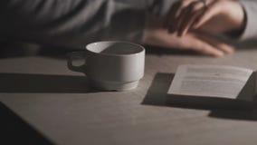 Dziewczyna siedział przy stołem z filiżanką kawy i książką zbiory wideo