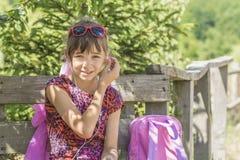 Dziewczyna siedział puszek odpoczywać słuchanie gracz z plecakiem dla podróży, Zdjęcie Royalty Free