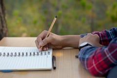 Dziewczyna siedział puszek pisać notatniku na drewnianym stole plan zdjęcie stock