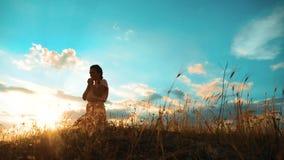 dziewczyna składał jej ręki w modlitewnej sylwetce przy zmierzchem Kobiety modlenia styl życia na jej kolanach zwolnionego tempa  zbiory wideo