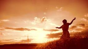 dziewczyna składał jej ręki w modlitewnej sylwetce przy zmierzchem kobiety modlenie na jej kolanach stylu życia zwolnionego tempa zbiory wideo