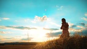 dziewczyna składał jej ręki w modlitewnej sylwetce przy zmierzchem kobiety modlenie na jej kolanach zwolnione tempo stylu życia w zdjęcie wideo