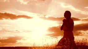 dziewczyna składał jej ręki w modlitewnej sylwetce przy zmierzchem kobiety modlenie na jej kolanach zwolnionego tempa wideo Pojęc zbiory
