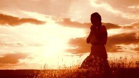 dziewczyna składał jej ręki w modlitewnej sylwetce przy zmierzchem kobiety modlenie na jej kolanach zwolnionego tempa wideo Pojęc zdjęcie wideo