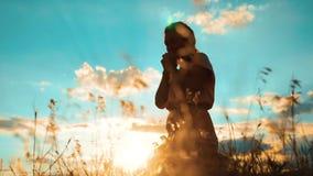 dziewczyna składał jej ręki w modlitewnej sylwetce przy zmierzchem kobiety modlenie na jej kolanach zwolnionego tempa wideo Dziew zdjęcie wideo
