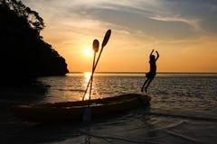 Dziewczyna skakał od kajaka na plaży przy zmierzchem Zdjęcia Stock