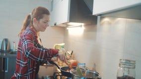 Dziewczyna smaży w griddle stojakach w kuchni indoors gotuje karmowych stojaki przy kuchenką kobieta stoi bezczynnie kuchenkę wew zbiory