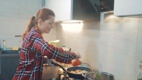Dziewczyna smaży w griddle stojakach w kuchni indoors gotuje karmowych stojaki przy kuchenką kobieta stoi bezczynnie kuchenkę wew zbiory wideo