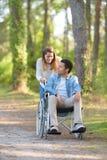 Dziewczyna spaceruje z niepe?nosprawnym partnerem na w?zku inwalidzkim zdjęcia royalty free