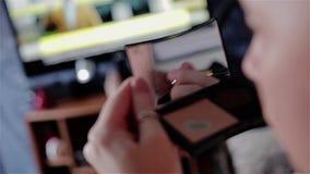 Dziewczyna stawia dalej jej twarzy makeup Widok za od ramienia przez małego lustra w rękach dziewczyna Bardzo piękny zbiory