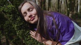 Dziewczyna stawia jej głowę na drzewnym bagażniku który zakrywa z mech i spada uśpiony zbiory