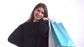 Dziewczyna stawia papierowe torby z rzeczami z powrotem za ona z jeden ręką, ono uśmiecha się i drepcze od jeden stopy inny, zbiory