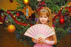 Dziewczyna stoi blisko dekorującej choinki z koroną na głowie zdjęcia royalty free