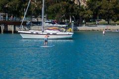 Dziewczyna stoi na paddle desce paddling na gładkiej błękitne wody obraz royalty free