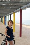 Dziewczyna stoi z jej bicyklem na dennej plaży fotografia stock