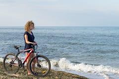 Dziewczyna stoi z jej bicyklem na dennej plaży obraz stock
