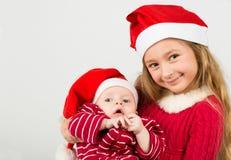 Dziewczyna stojak w Święty Mikołaj kapeluszach i mienie chłopiec Zdjęcia Stock